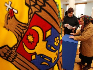 Women cast their ballots at a polling station during the parliamentary election next to a Moldova national flag in Chisinau