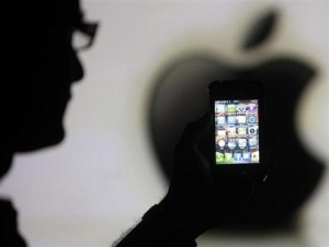 Man poses with Apple iPhone 4 smartphone in photo illustration in Zenica