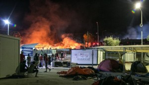 Migrants and riot police stand outside the Moria refugee camp as a fire